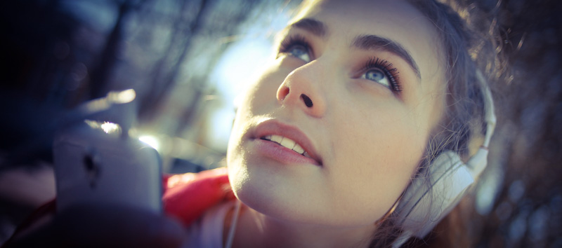 Junge Frau lernt mit Hueber Grosser Hörkurs Englisch mit Handy